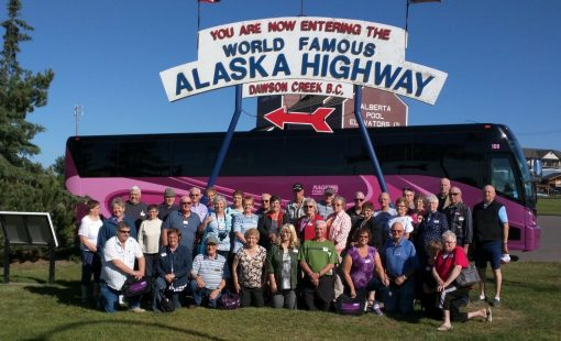 Contact us to be in a group like this one in front of a Nagel Coach at Alaska HIghway Mile 0