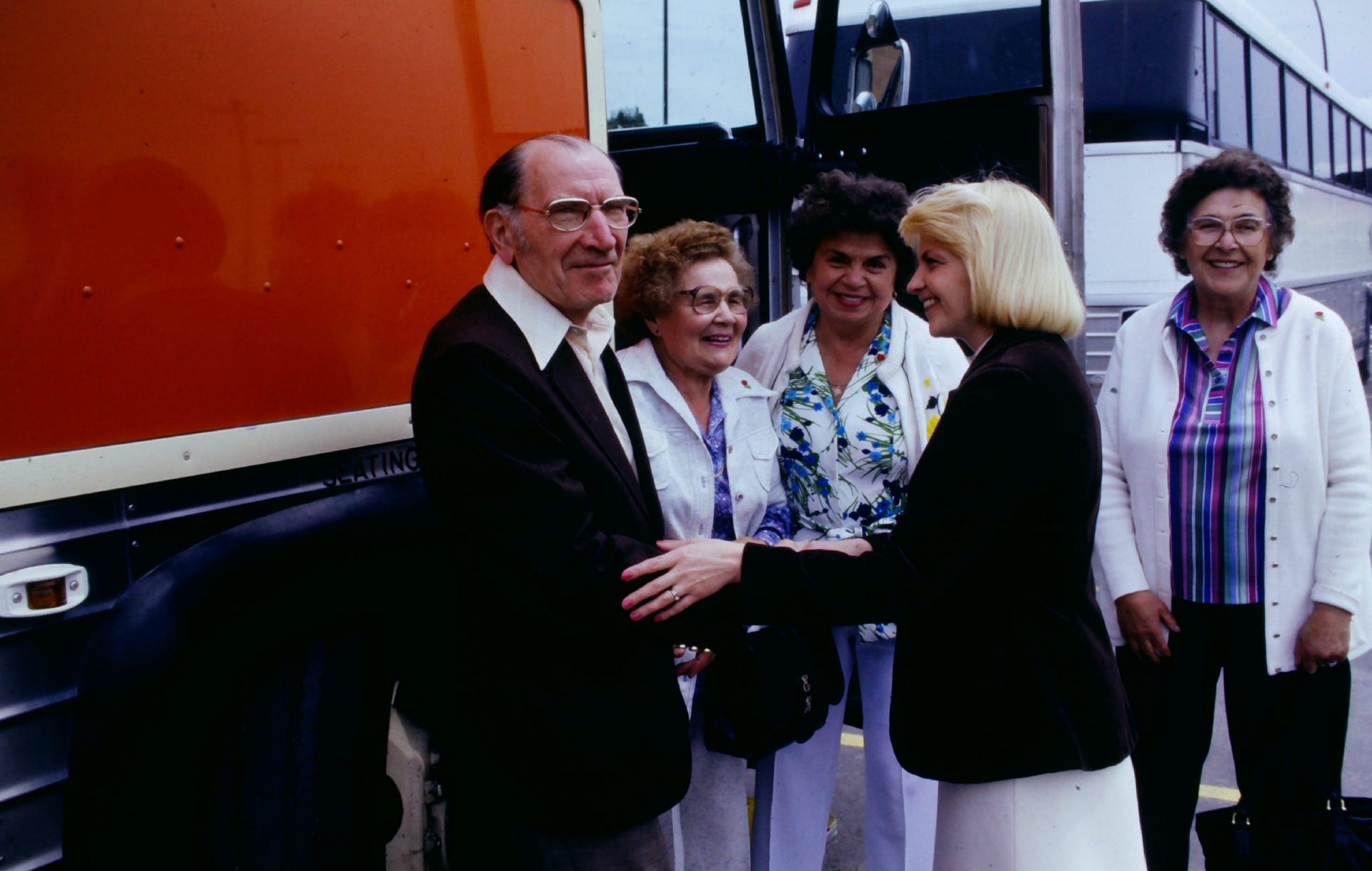 Passengers outside coach greeted by Tour Director 1970s