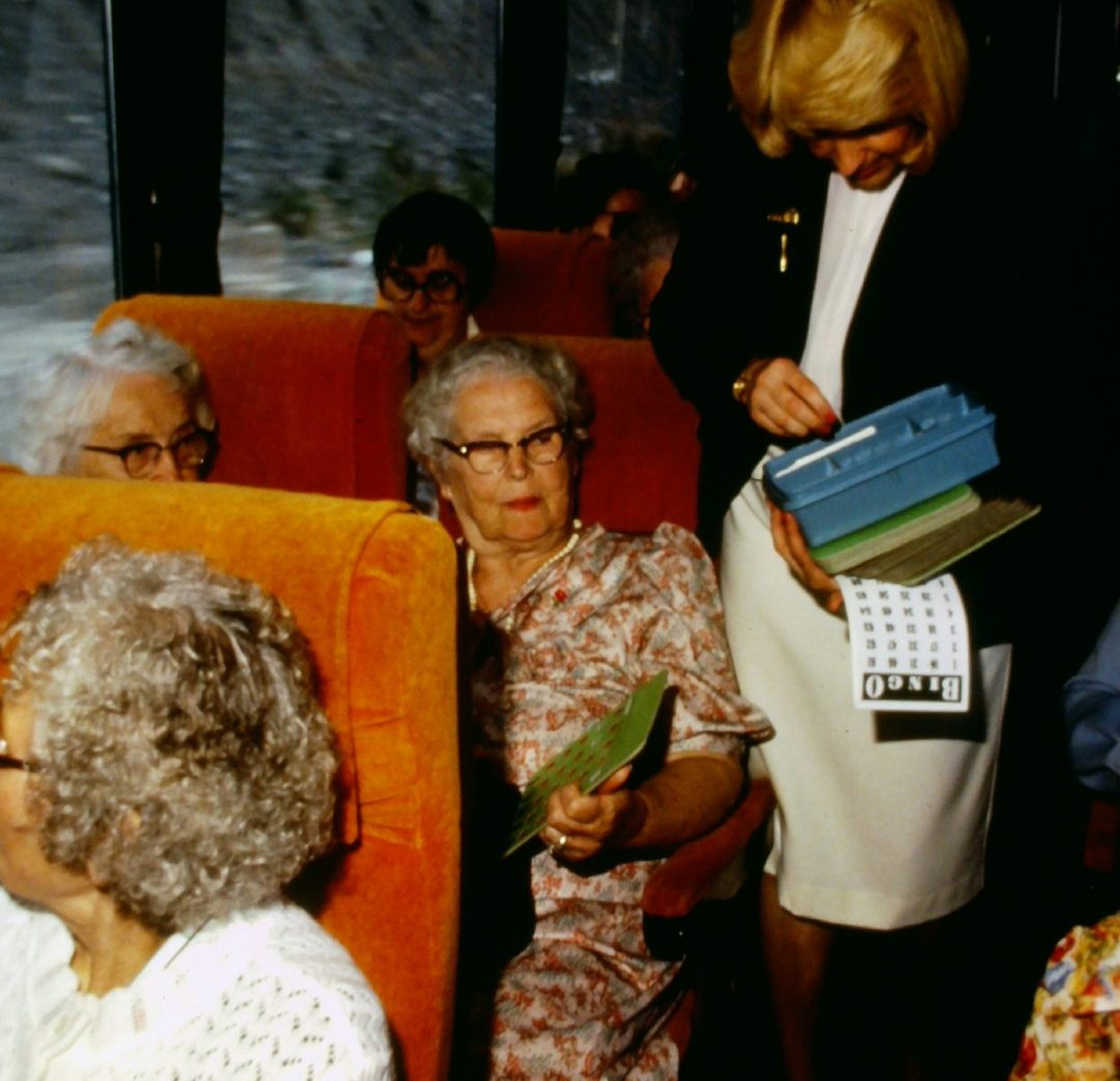 Passengers on coach with Tour Director bingo playing 1970s